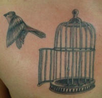 Bird flying out of bird cage tattoo